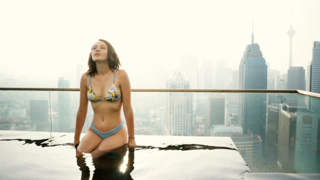 Woman in the swimming pool with view of Kuala Lumpur