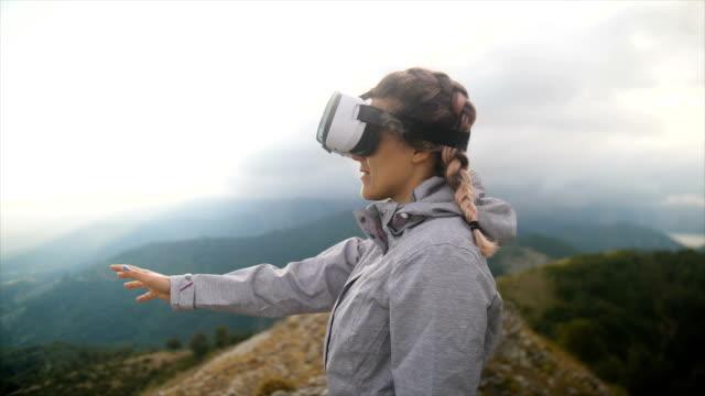 vídeos y material grabado en eventos de stock de woman in the top of a mountain with virtual reality glasses - realidad virtual