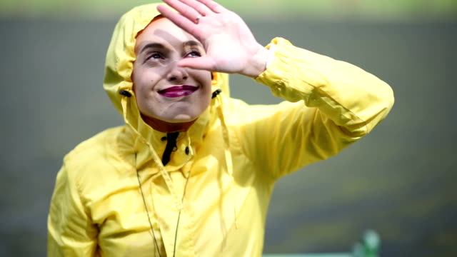 woman in the yellow rain coat outdoors - raincoat stock videos & royalty-free footage