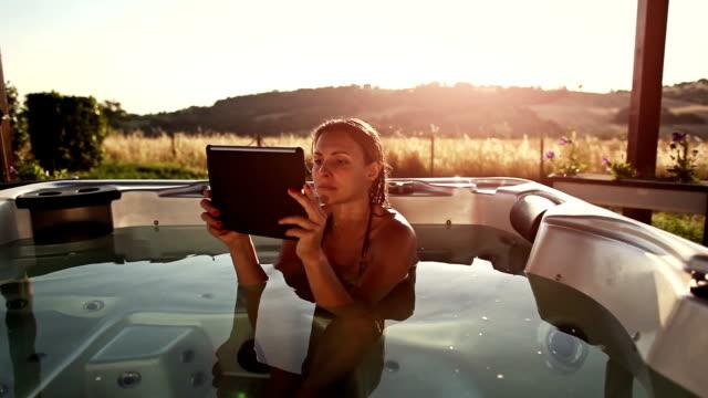 vídeos de stock, filmes e b-roll de mulher na thermal banheiro com tablet digital - banheira
