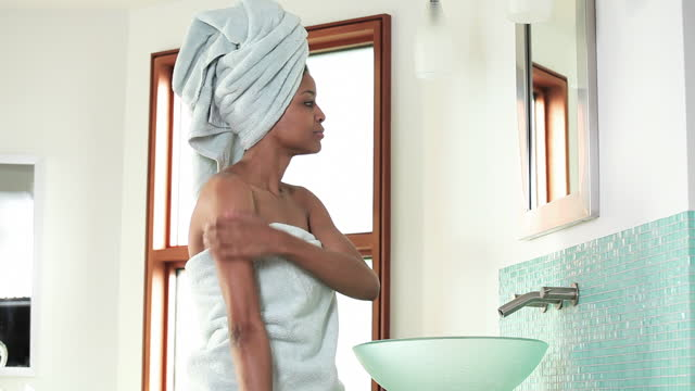 Woman in towel applying lotion to shoulders, hands and face in bathroom mirror