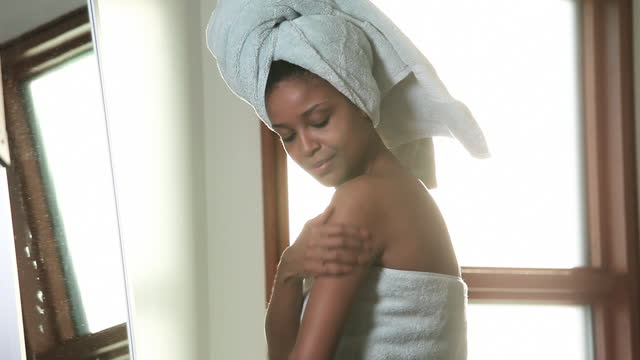 woman in towel applying lotion to shoulders, hands and face in bathroom mirror - day in the life stock videos & royalty-free footage
