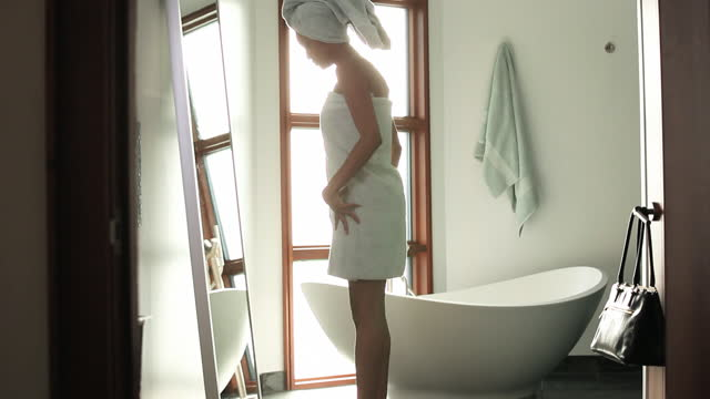 woman in towel stepping on scale in front of full length bathroom mirror - 体重計点の映像素材/bロール
