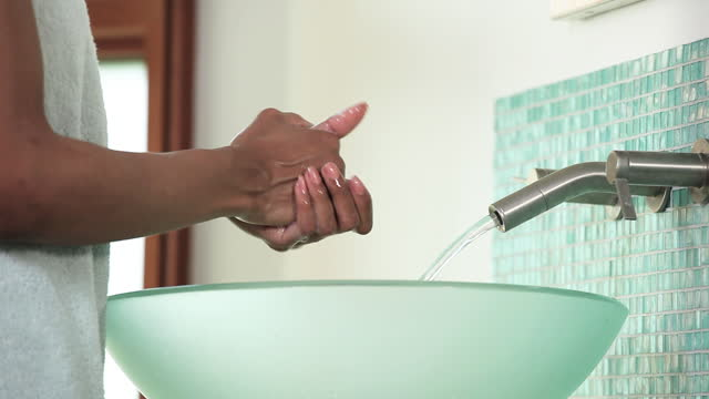 Woman in towel washing hands with soap in bathroom sink