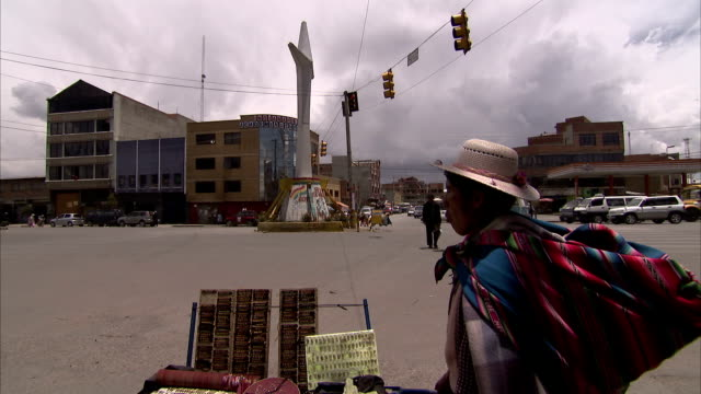 A woman in traditional Bolivian dress stands at the edge of a city intersection. Available in HD.