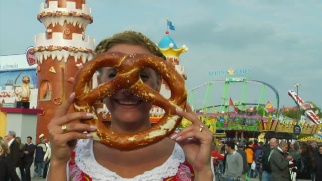 cu woman in traditional clothes posing with pretzel, oktoberfest, munich, germany - german culture stock videos & royalty-free footage
