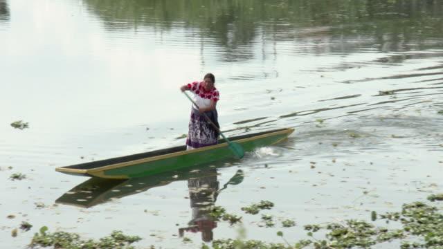ws ts woman in traditional dress paddling in small canoe / patzcuaro, michoacan, mexico - michoacán video stock e b–roll