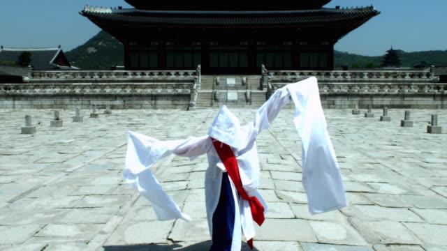 MS ZO TU Woman in traditional dress performing Buddhist Dance behind Gyeongbokgung Palace / Seoul, South Korea