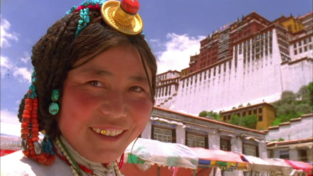 vidéos et rushes de woman in traditional dress smiles at camera outside potala palace available in hd. - coiffe traditionnelle