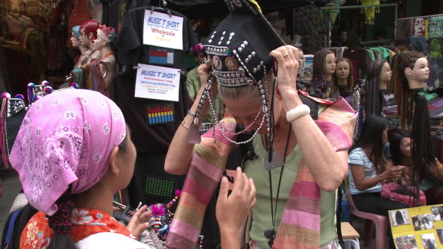 ms woman in traditional hat photographing self with female market vendors, bangkok, thailand - thailand video stock e b–roll