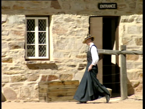 woman in traditional outfit walks towards and enters dormitory of former 'stolen generation' aborigine camp alice springs - the past stock videos & royalty-free footage