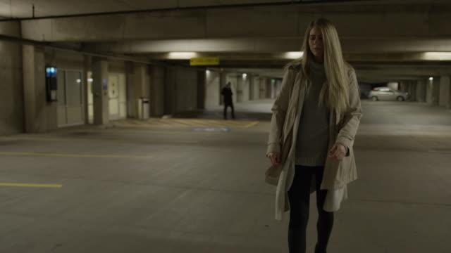 woman in underground parking garage worried about man following her / provo, utah, united states - provo stock-videos und b-roll-filmmaterial
