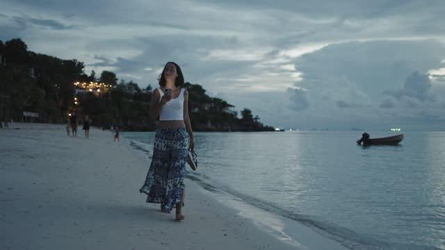 vídeos de stock, filmes e b-roll de mulher em usar celular à beira-mar - vista de ângulo baixo
