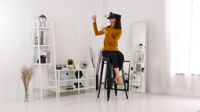 vidéos et rushes de femme dans le casque virtuel de réalité à la maison - invisible