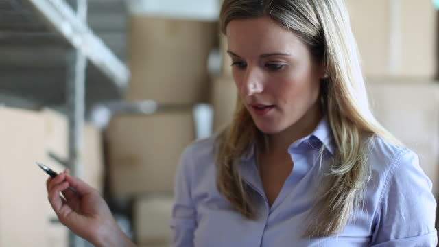 "stockvideo's en b-roll-footage met ""cu of woman in warehouse inspecting boxes in handed clipboard to sign then hands it back / brooklyn,new york,united states"" - directrice"