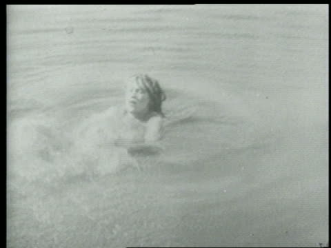 B/W 1915 woman in water catching rope thrown to her / short