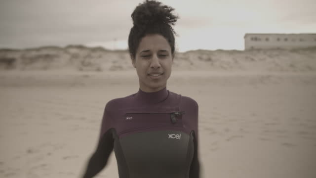 woman in wetsuit at beach warming up arms and shoulders before going surfing - wetsuit stock videos & royalty-free footage