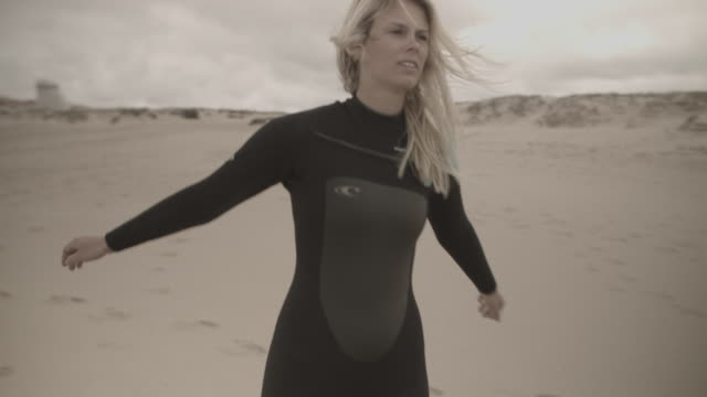 Woman in wetsuit stretching shoulders at beach before going surfing