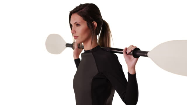 Woman in wetsuit with kayak paddle over shoulder facing side on white copy space