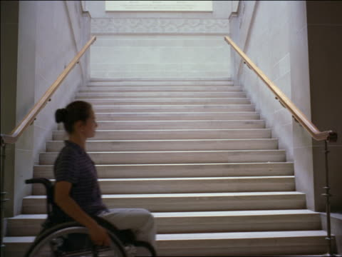 woman in wheechair stopping in front of stairs / looking up at stairway - disability stock-videos und b-roll-filmmaterial
