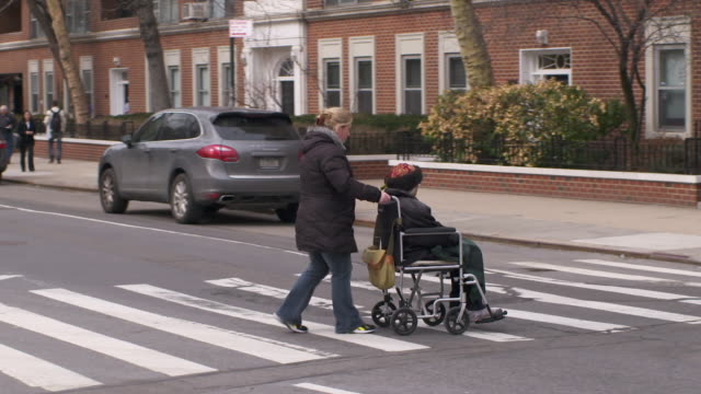 woman in wheelchair being pushed across the street in greenwich village - schieben stock-videos und b-roll-filmmaterial