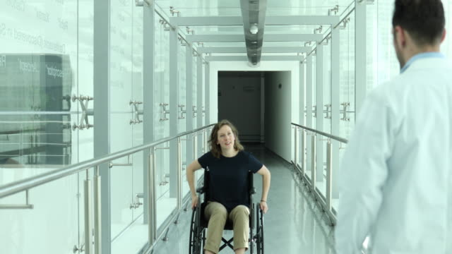 Woman in wheelchair greeted by medical professional