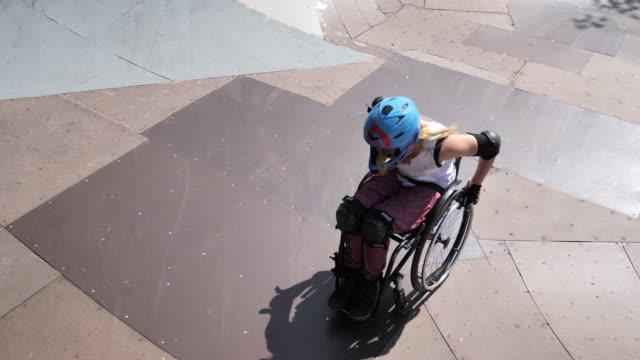 vídeos y material grabado en eventos de stock de mujer en silla de ruedas en el parque de patinaje - generation z
