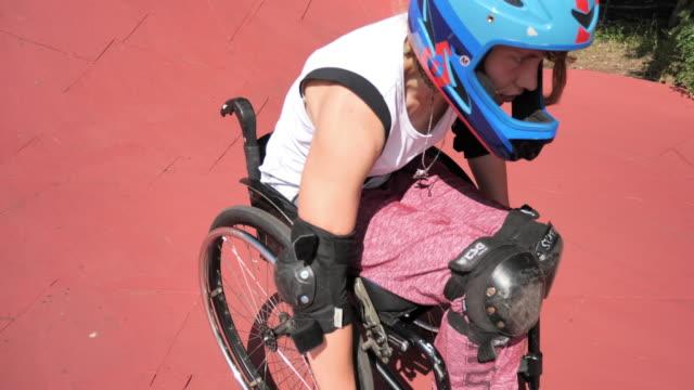 vídeos de stock, filmes e b-roll de mulher na cadeira de rodas no parque do patim - cadeira de rodas equipamento ortopédico