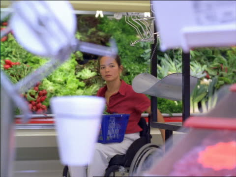 woman in wheelchair moving towards scale in produce department in supermarket - paralysis stock videos & royalty-free footage