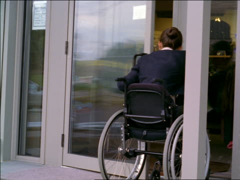 woman in wheelchair opening door + entering clothing store - wheelchair stock videos & royalty-free footage