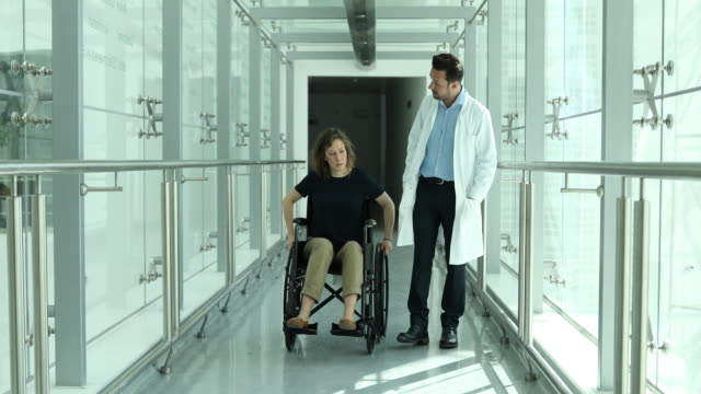 Woman in wheelchair talking with medical professional