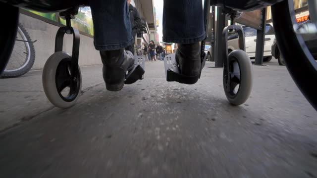 vidéos et rushes de woman in wheelchair traveling across the city - chaise roulante