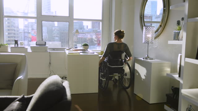 woman in wheelchair working from home office. - loft apartment stock videos & royalty-free footage