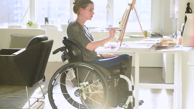 woman in wheelchair working on a painting from her home. - 車いす点の映像素材/bロール