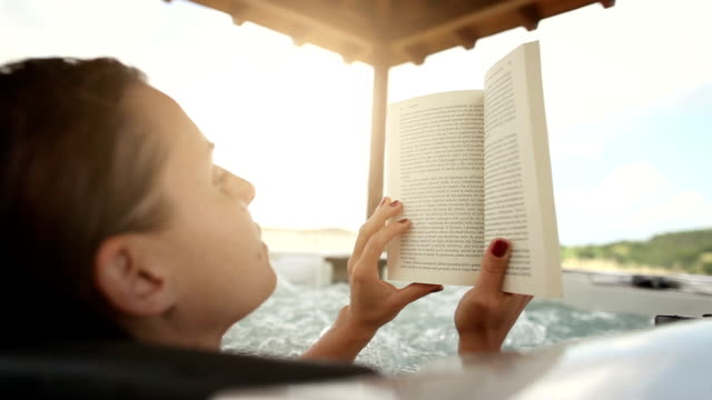 Woman in whirlpool hot tub reading a book