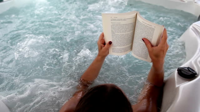 woman in whirlpool hot tub reading a book - whirlpool stock videos & royalty-free footage
