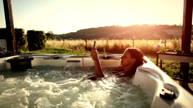woman in whirlpool hot tub with digital tablet - spa treatment stock videos & royalty-free footage