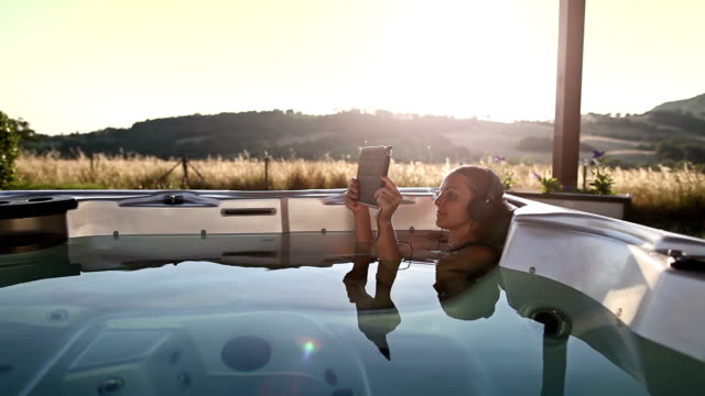 Woman in whirlpool hot tub with digital tablet