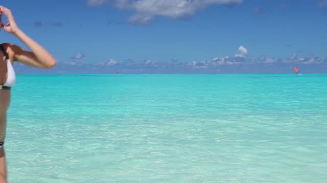 woman in white bikini walking through blue lagoon - solo una donna di età media video stock e b–roll