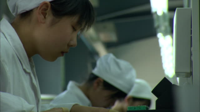 cu la selective focus woman in white coat soldering parts used to make solar hot water heaters, dezhou, shandong, china - fließband stock-videos und b-roll-filmmaterial