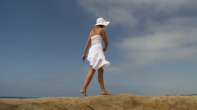 Woman in white dress and white hat prances on sand berm at the beach