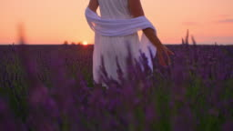 LA Woman in white dress in a field of lavender at dusk