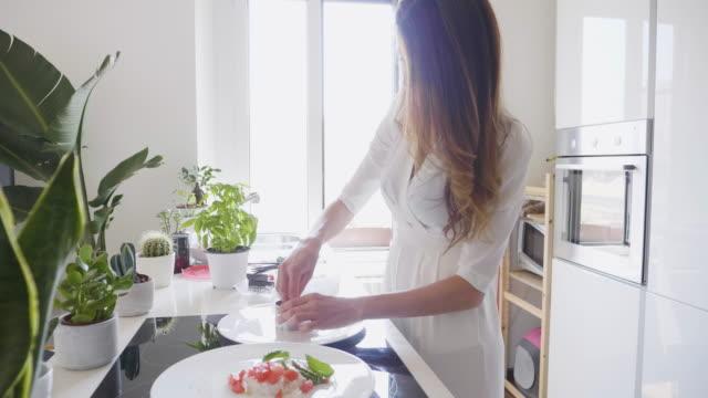 woman in white dress preparing sushi in kitchen - weißes kleid stock-videos und b-roll-filmmaterial