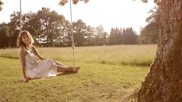 SLO MO PAN Woman in white dress relaxing on swing