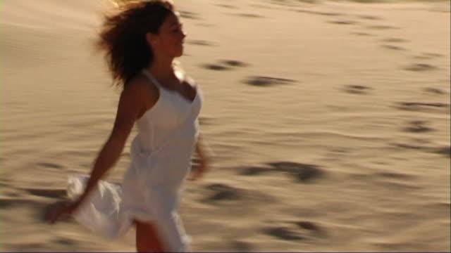 vidéos et rushes de woman in white dress running on beach - robe blanche