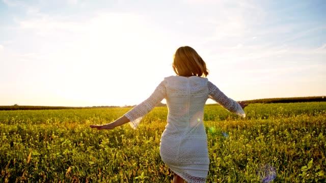 SLO MO femme en robe blanche en cours d'exécution sur l'herbe