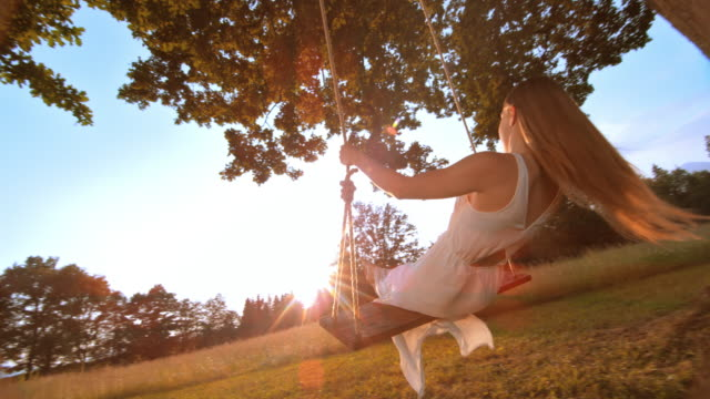 SLO MO Woman in white dress swinging at sunset