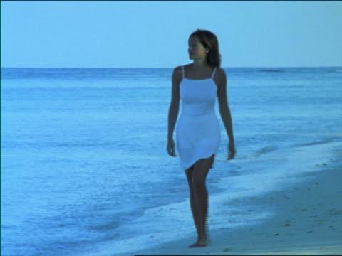 blue woman in white dress walking on beach next to ocean / seychelles - weißes kleid stock-videos und b-roll-filmmaterial