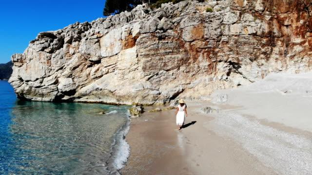 woman in white dress walking on beach. - white dress stock videos & royalty-free footage