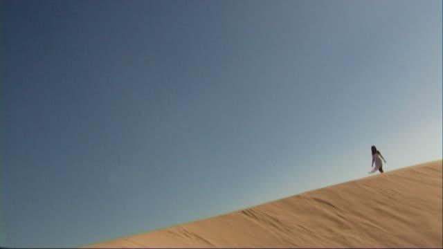 stockvideo's en b-roll-footage met woman in white dress walking on beach - witte jurk